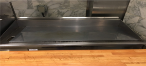 A grill's flat metal surface that is used to cook ingredients.