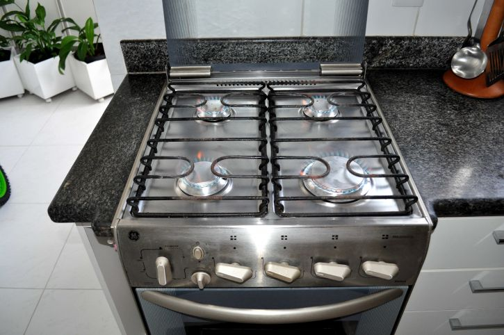An oven with a gas burner stove on top is shown. Black metal rod grates allow pots and pans to sit atop the flames.