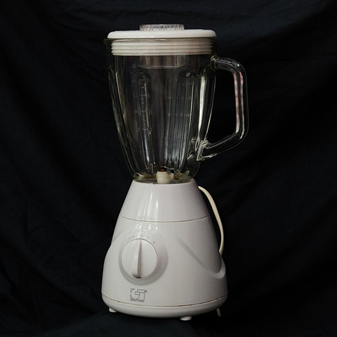 image of a white blender with a rotating metal blade at the bottom