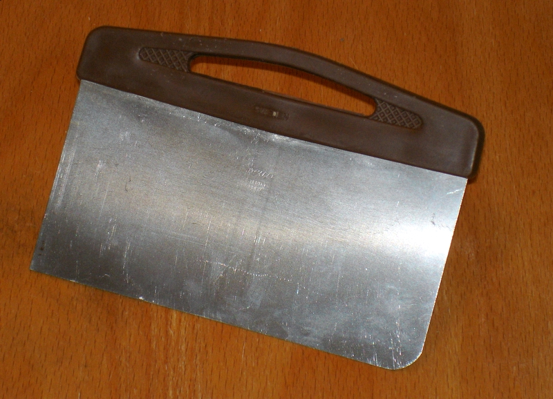 image of a bench knife, a straight-edged metal rectangle with a handle along one side