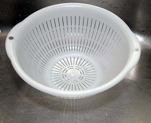 image of a white colander in a sink