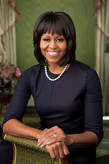 Michelle Obama poses for a portrait picture in a black silk dress and pearls.