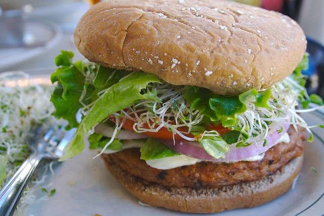 Veggie burger on bun with lettuce, tomato, onion and sprouts.