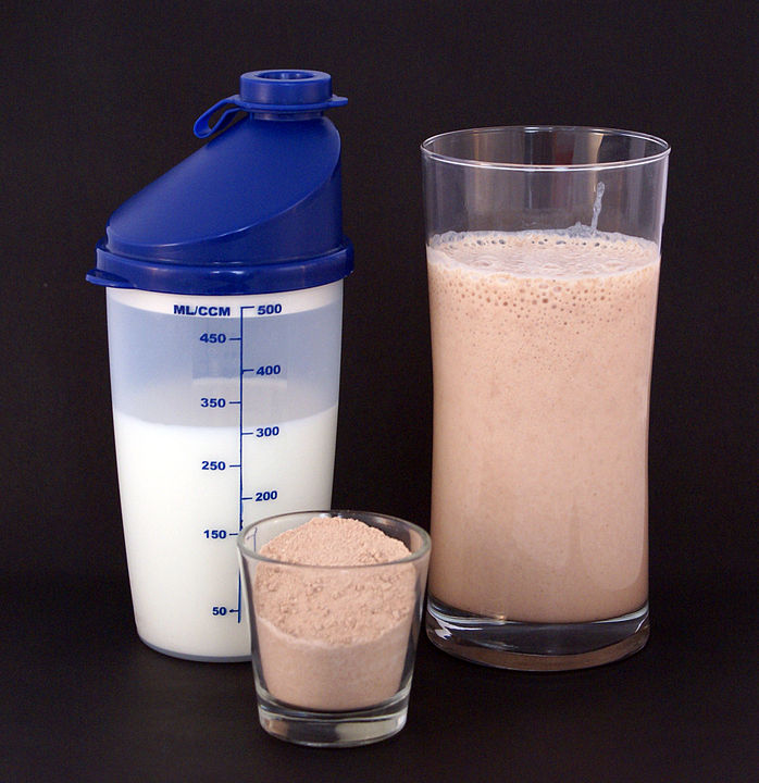 A glass of milk, a small glass with tan powder and the 2 ingredients combined into a shake.
