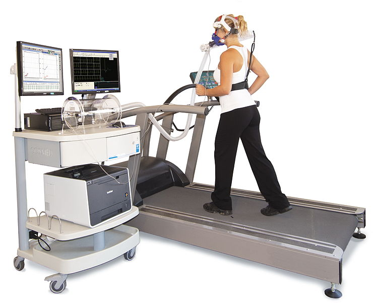 Woman on treadmill wears oxygen mask with hoses connected to a computer