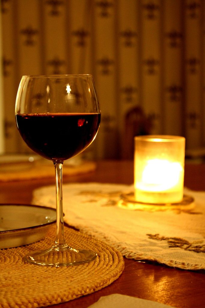 A glass of red wine alongside a candle lamp.