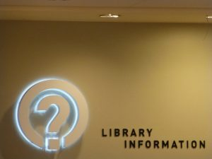 The front desk of the Berkeley Public Library with the text Library information, and a icon for a question mark surrounded by a circle.