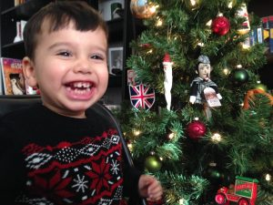 A boy smiles. The Christmas tree has ornaments including the Union Jack and Sherlock Holmes.