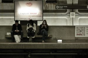 Three people sitting under a advert looking at their phone while waiting for a train.