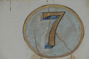 A handpainted gold number 7 with a light blue circle, and a gold border.