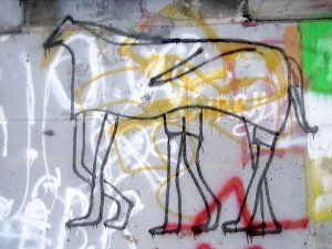 A Graffiti wall with a painting of three-person horse