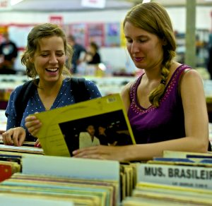 A women discussing and selecting a vinyl record