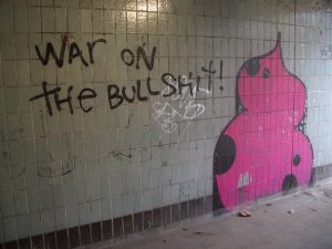 "A spray paint on a wall saying ""war on the bullshit"" next to a pink stool"