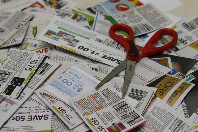 A pile of coupons with a scissor resting on them.