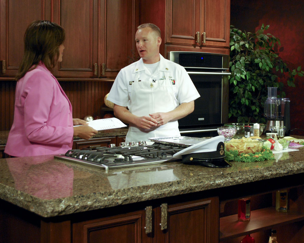 A cooking show host and guest behind a counter talking and preparing the recipe.