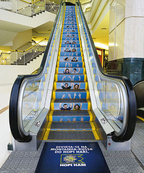 An escalator with an ad for a roller coaster