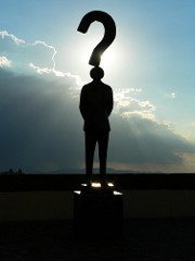 Silhouette of a man as the dot in the question mark standing in front of the sun.
