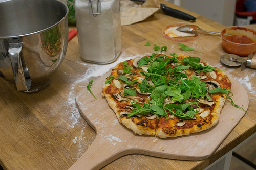 Image of a pizza with mushroom and arugula.