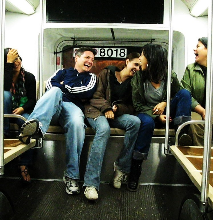 A group of friends sit in the back of a bus laughing together.