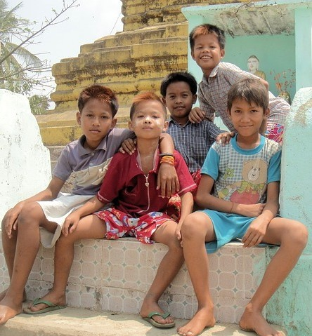 A group of young boys sit together on the steps with their arms around one another.