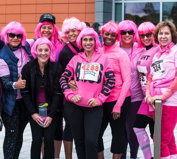 A group of women wearing pink wigs and pink shirts pose together at the conclusion of a 5K race in support of those with breast cancer.