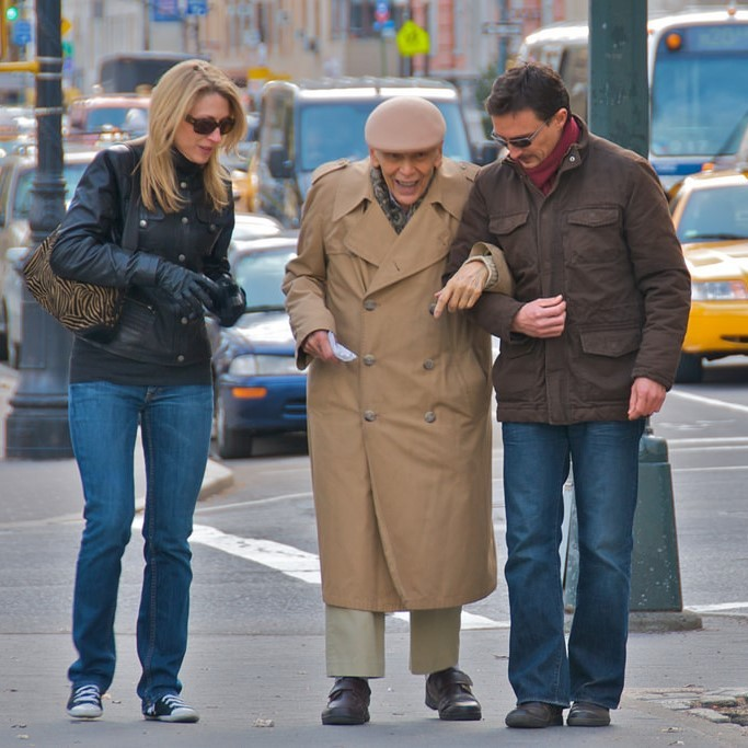 A younger man and woman help an elderly gentleman down the street.