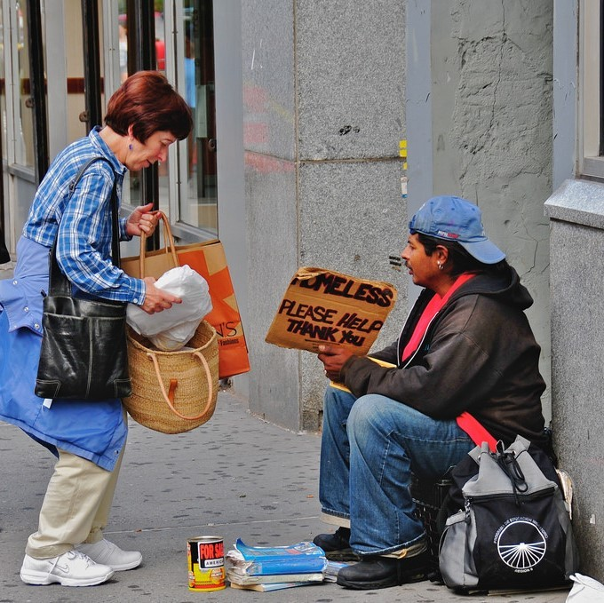 "A woman stops on the sidewalk to offer food to a man holding a sign reading ""Homeless, please help Thank you."""