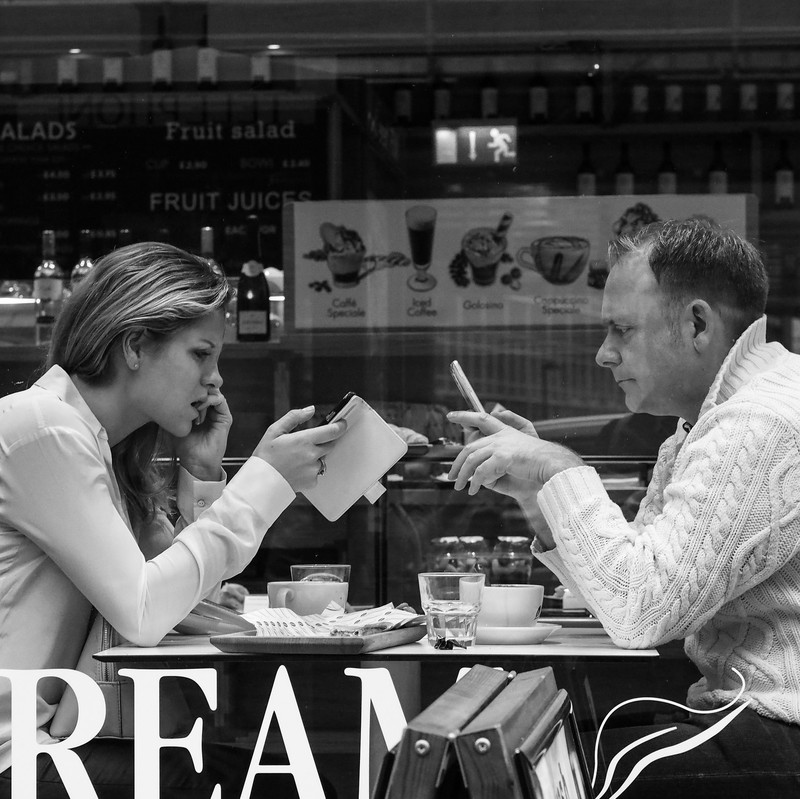 A man and a woman sit across from one another at a small table in a coffee shop. Both of them are staring at their own smartphone rather than engaging with each other.