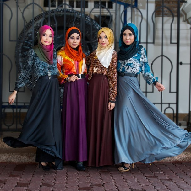 A group of Malaysian fashion models pose in colorful headscarves, long-sleeved blouses, and floor-length dresses.