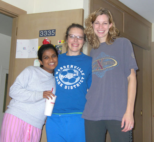 Three college friends stand together in a dorm room. The woman on the right is 6 inches taller than the woman in the middle. The woman in the middle is six inches taller than the woman on the left.