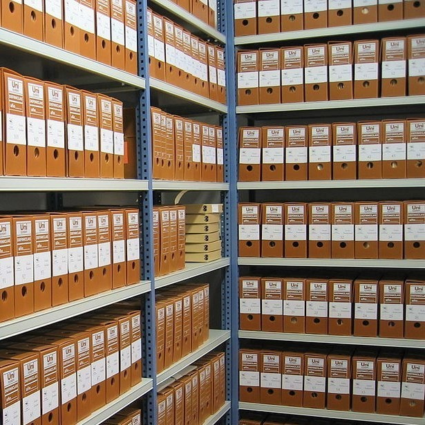 Archive shelves full of document binders.