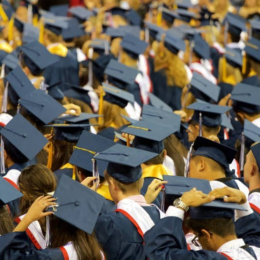 College graduates stand in caps and gowns during a commencement ceremony.