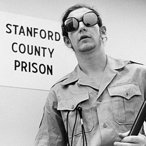 Photo of a participant guard from the Stanford Prison Experiment wearing sunglasses and holding a truncheon.