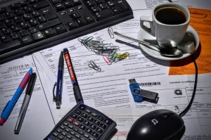 photo of cluttered desk with calculator, cup of coffee, paperclips, keyboard and paper forms.