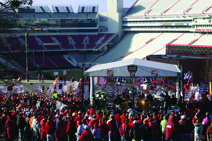 A photograph shows a crowd of people standing near a stadium at a tent.