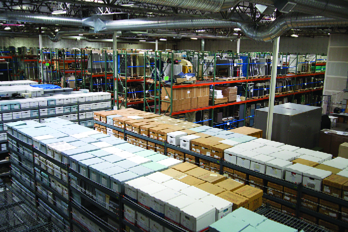 Photo of a factory floor, showing stacks of boxes.