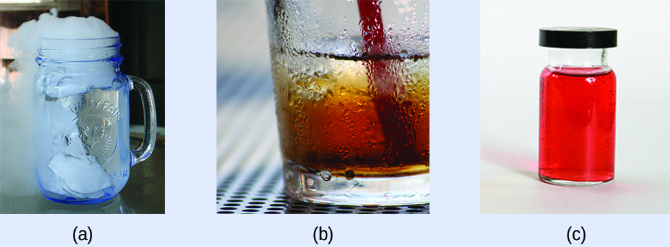 """This figure has three photos labeled, """"a,"""" """"b,"""" and """"c."""" Photo a shows a glass with a solid in water. There is steam or smoke coming from the top of the glass. Photo b shows the bottom half of a glass with water sticking to its outside surface. Photo c shows a sealed container that holds a red liquid."""