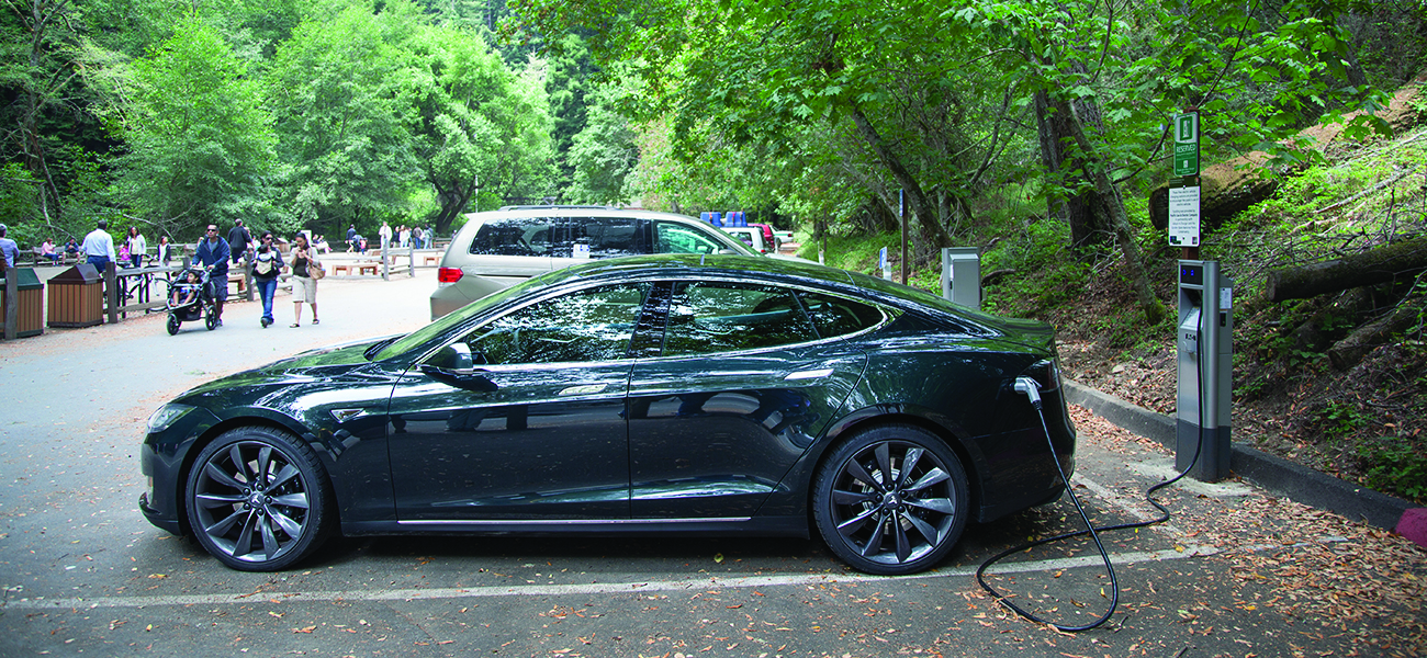 A photograph is shown of a parked car plugged into a charging station in a paved parking area. The parking area is situated in a wooded area. People are walking in the background in the park-like atmosphere.