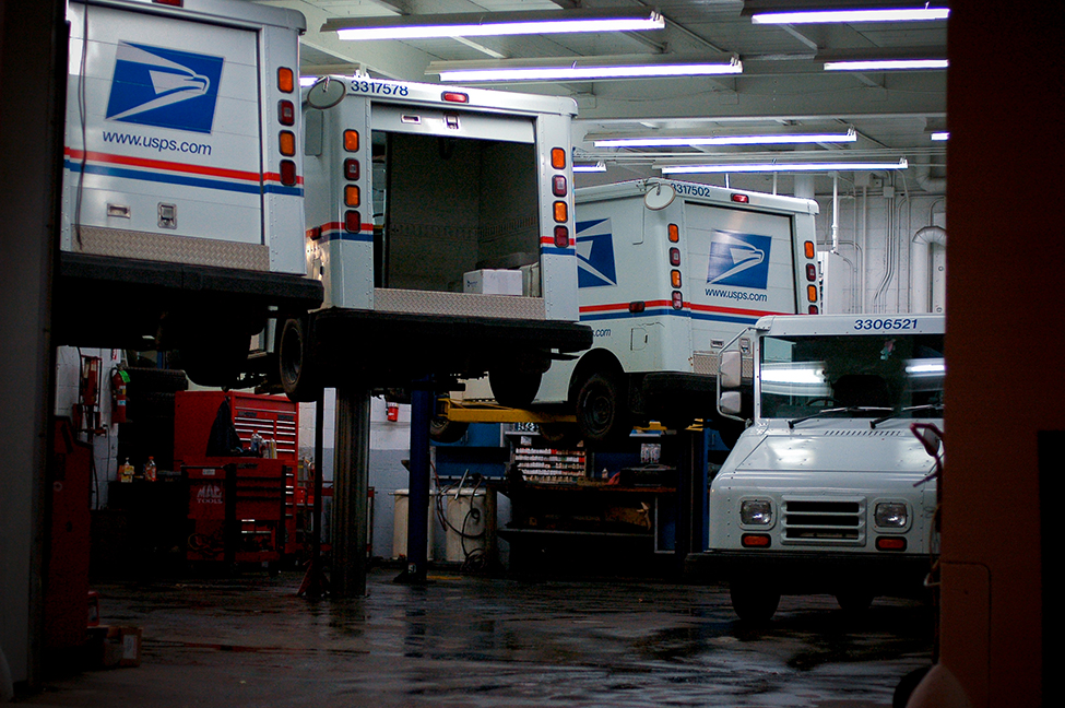 This is a photo of a car mechanic's shop. There are three United States Postal Services trucks being serviced, and one not being serviced.