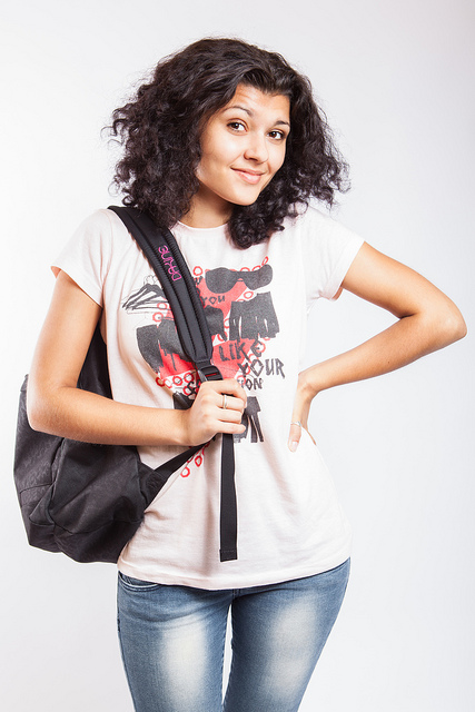 A college student standing unsure with her backpack