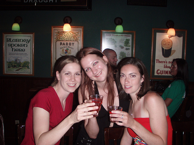Three women taking shots at a 21st birthday party