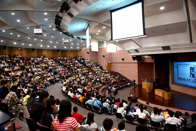 A giant lecture hall using the visual aids of a large projector and a TV