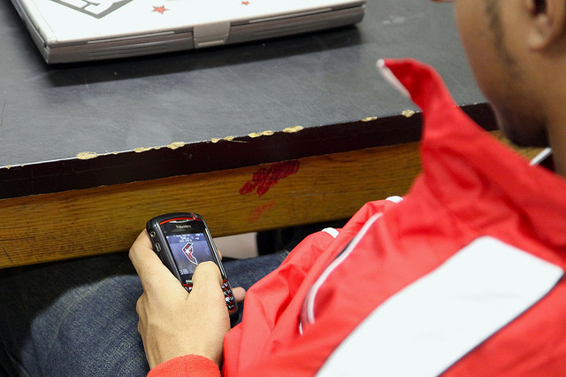 A student sneakily using his cell phone while in class