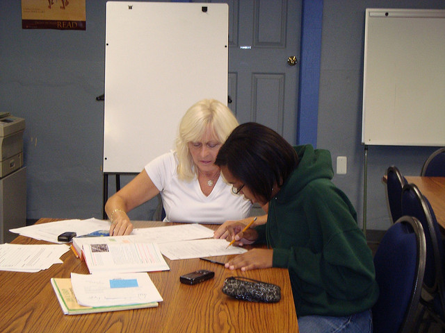 A student at office hours, meeting with her professor