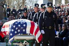 A group of police officers carry a casket at a memorial service.